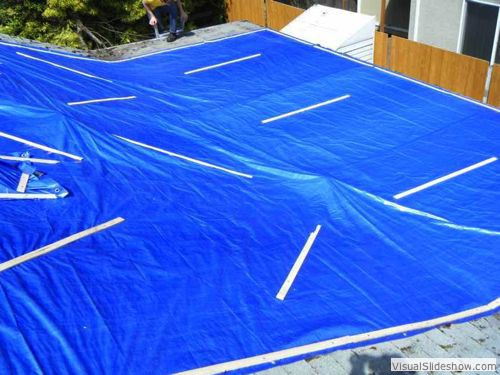 After - Flat roof tarped; tarp must extend up roof and over ridge